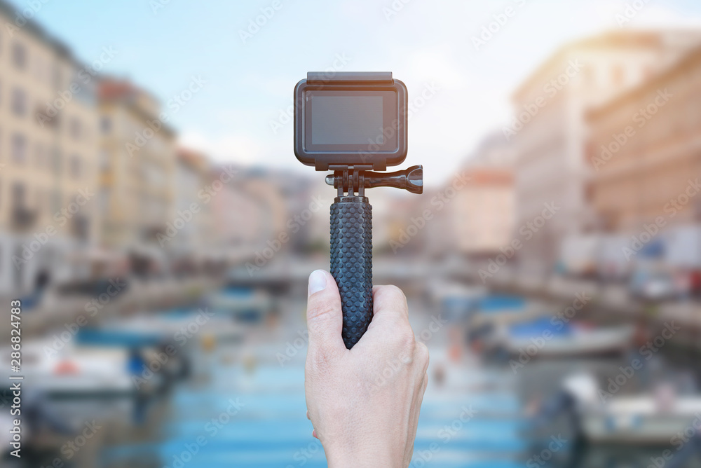 Fototapeta Action camera on stick in hand recording city concept. Blank screen for mockup.
