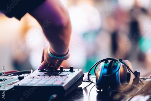 Electronic music festival in summer.EDM dj plays set on stage at concert.Disc jockey playing popular music on midi controller device & headphones on table.Professional audio equipment for djs - 286825307