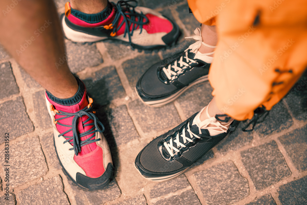 Fototapety, obrazy: Couple legs in footwear standing together on pavement at night