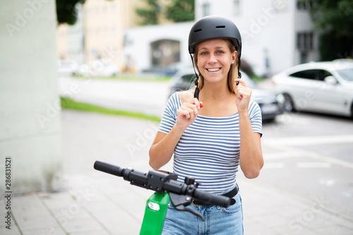 Junge Frau zieht einen Helm an um mit einem E-Scooter zu fahren Tablou Canvas