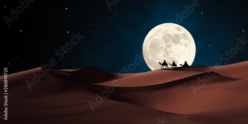 Fotografiet Three wise men riding on camels traveling in the desert