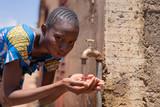 Fototapeta Łazienka - Close-up Photograph: African Black Teenage Girl Drinking Water
