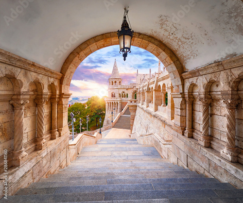 Foto auf Leinwand Budapest Budapest, Hungary. Ancient Fishermans Bastion castle. View at tower from stairs under arch along gallery with columns and street lantern. Picturesque evening sunset with clouds on sky. Famous.