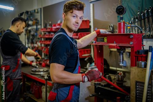 Photo Car mechanic working on a hydraulic press in a workshop