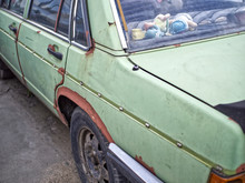 Old And Rusty Car In Green