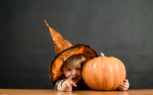 Little Boy In Witch Hat With Halloween Pumpkin Pointing To You. Trick Or Treat. Preparation Halloween Holiday. Happy Halloween. Halloween Party. Witch Costume. 31 October. Child With Pumpkin. Autumn.