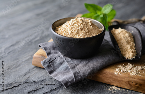 Fotografie, Obraz  Dietary supplement, Maca root powder in a bowl and scoop with copy space