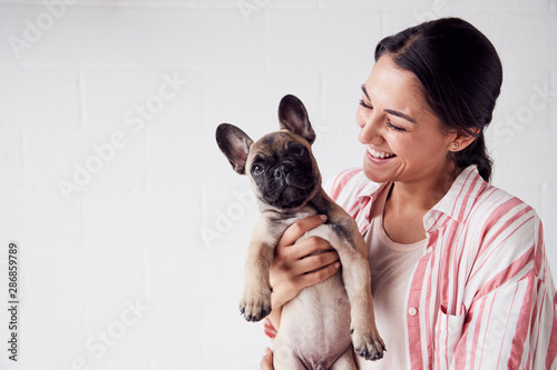 Fotografie, Obraz  Studio Shot Of Smiling Young Woman Holding Affectionate Pet French Bulldog Puppy