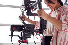 Female Videographer With Video Camera On Steady Cam Rig Filming Movie In White Studio