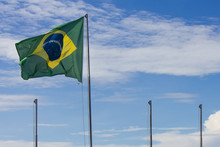 National Flag Of Brazil, Swaying In The Wind, Next To Three Other Empty Flagpoles, With A Slightly Cloudy Blue Sky Background.