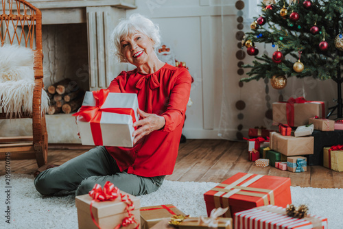 Happy old lady is holding Christmas present - 286870715
