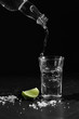 Pouring vodka into the shot glass on a black background with a blank space for a text, Russian vodka with salt and lemon