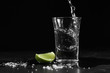 close up pouring vodka into the shot glass on a black background, Russian vodka with salt and lemon