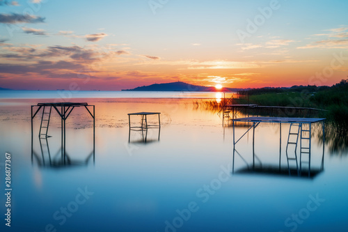 Fototapeta sunrise with sun peaking out of the mountain at lake balaton hungery, with nice