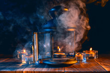 Halloween Concept, Spooky Decorations With Lighting Up Candle And Candle Holder With Blue Tone Smoke Around On A Dark Wooden Table, Close Up.