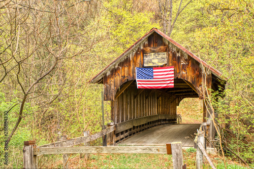A covered bridge, long abandoned, still stands in the countryside despite being neglected with weathered wood Canvas Print
