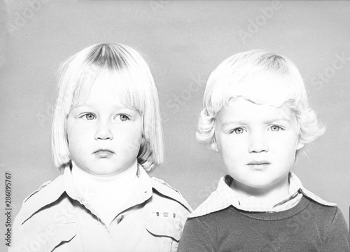 Photo Monochrome 1978 portrait of a side-eyeing girl with blond hair and a boy with blond hair looking at the camera