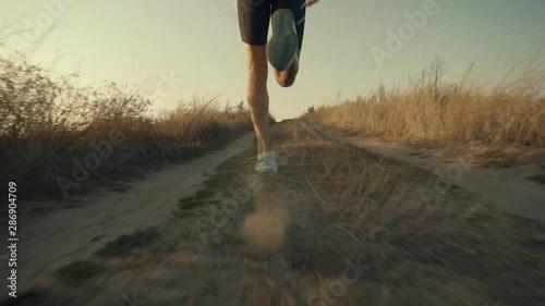 Running Man At Sunset .Runner Marathon Jog On Trail.Runner Man Fit Athlete Legs Jogging On City Prepares To Triathlon.Triathlete Running,Sprinting And Workout Endurance Training.