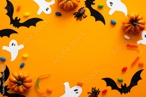 Happy halloween holiday concept. Halloween decorations, pumpkins, bats, candy, ghosts, bugs on orange background. Halloween party greeting card mockup with copy space. Flat lay, top view, overhead.