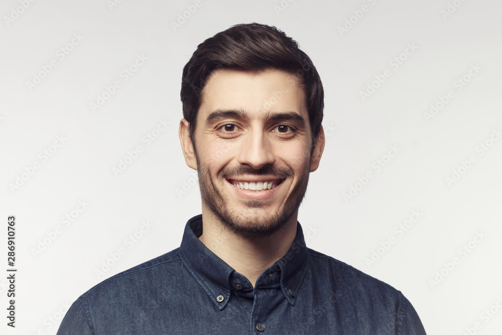 Fototapeta Close-up portrait of young smiling man in denim shirt isolated on gray background