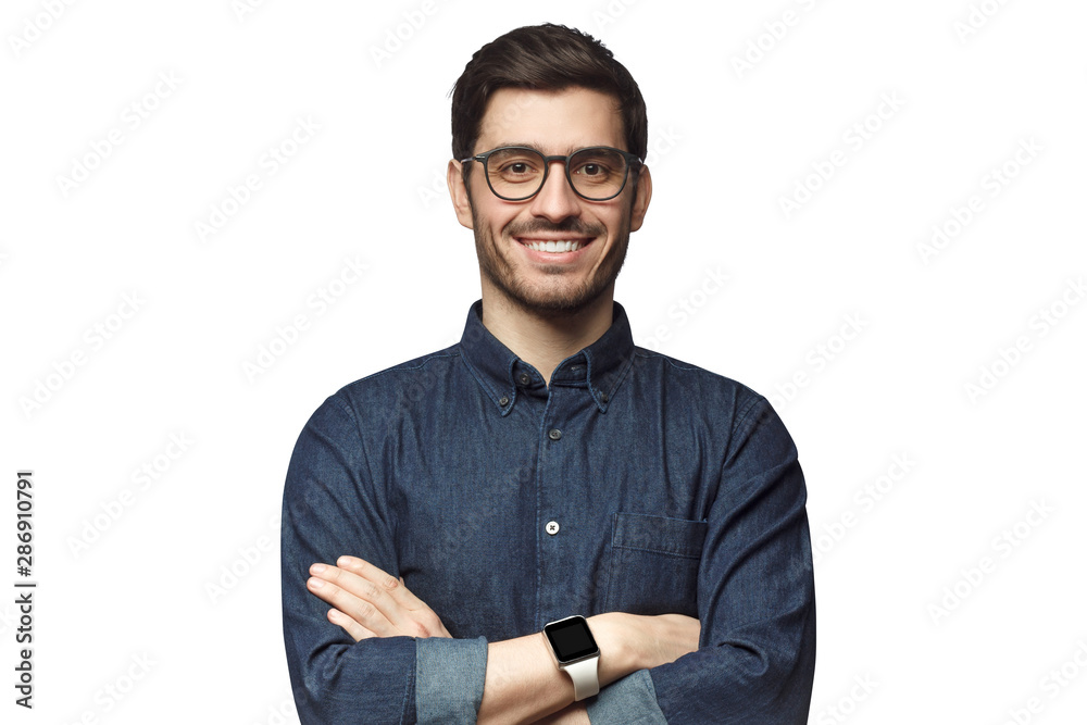 Fototapeta Portrait of young smiling caucasian man with crossed arms, wearing smart watch and casual denim shirt, isolated on white
