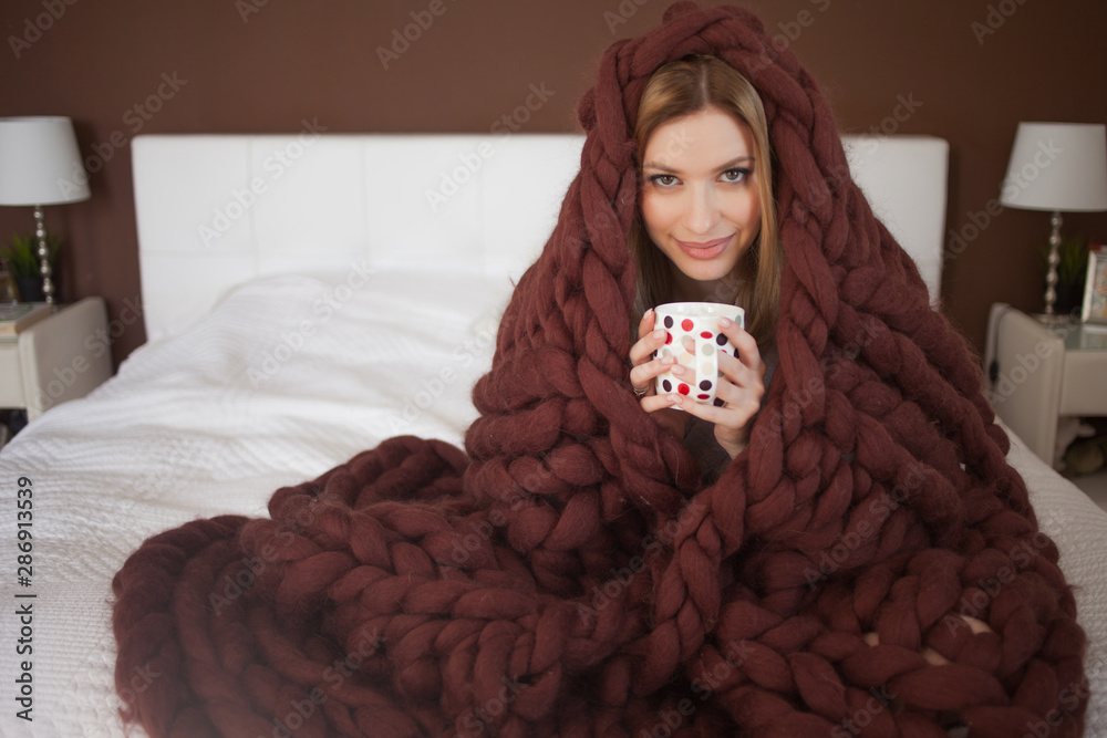 Fototapeta cute young woman is sitting on the bed wrapped in a big and fluffy brown plaid. Beautiful girl in a cozy blanket