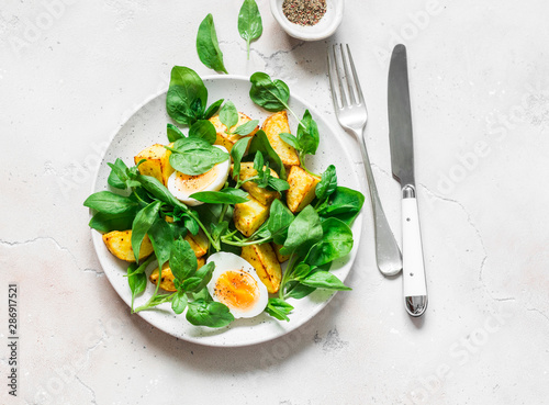 Fototapeta Baked potato, boiled egg and spinach salad on light background, top view obraz