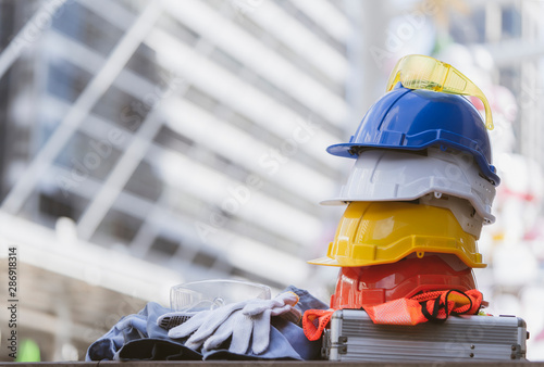 Obraz na plátně  white, yellow and blue hard safety helmet hat for safety project of workman as engineer or worker, on concrete floor in construction site