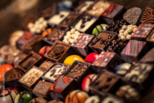Assorted chocolate pralines on the wooden background