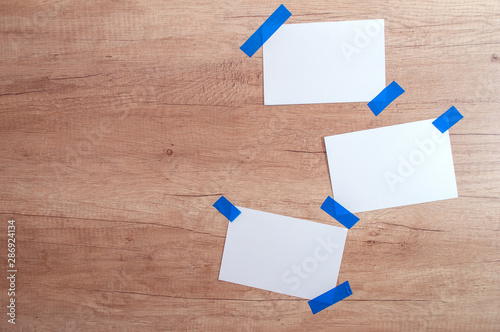 three White paper sheet attached with blue ribbon tape wooden background Wallpaper Mural