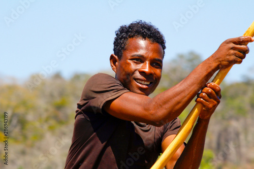 Photo Young Malagasy rafter man rowing traditional canoe on river, Madagascar