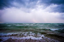 Dramatic Stormy Weather View Of Tropical Waves With An Infestation Of Brown Sargassum Seaweed Washing Ashore Under A Dark Rain Squall