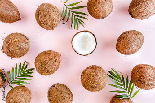 Pattern, texture with coconuts and tropical palm leaves on pink background Fototapeta