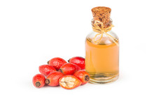 Glass Bottle Of Rosehip Seed Essential Oil With Fresh Rose Hip Fruits Isolated On White Background. Dogrose Oil With Fresh Dog Roses