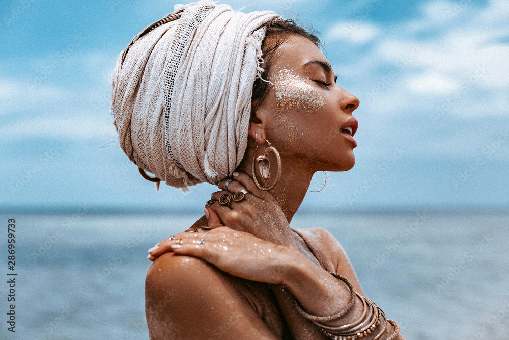 Fototapeta close up portrait of beautiful young tribal woman in turban at blue sea and sky background