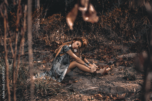 fototapeta na lodówkę beautiful young boho style woman sitting on ground outdoors