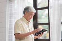Asian Elderly Man Using Tablet...