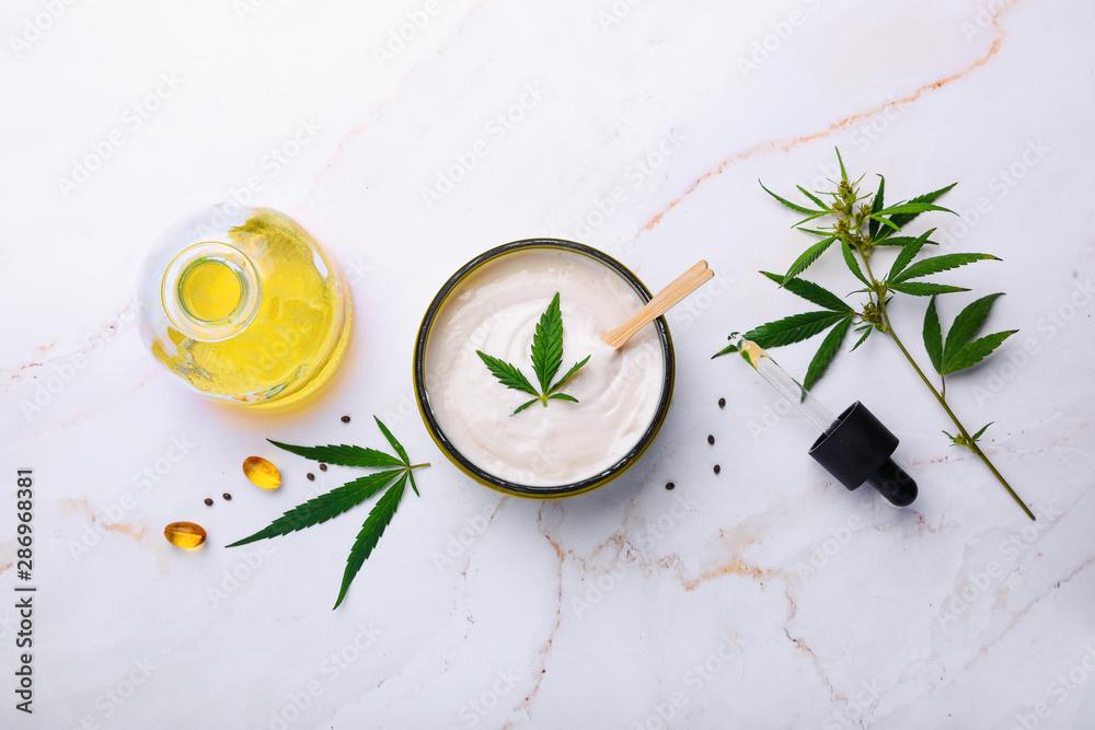 Fototapety, obrazy: Jar of hemp white lotion. Cannabis cream with marijuana leaf - cannabis concept. Flat lay, top view.