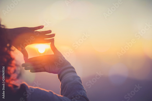 Fotografía  The woman making frame round the sun with her hands in sunrise,Future planning idea concept