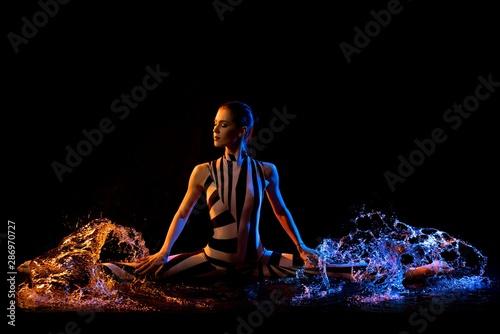 Slim model shot in water drops in the dark