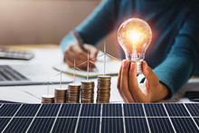 Businesswoman Holding Light Bulb With Turbine On Coins And Solar Panel. Concept Saving Energy And Finance Accounting