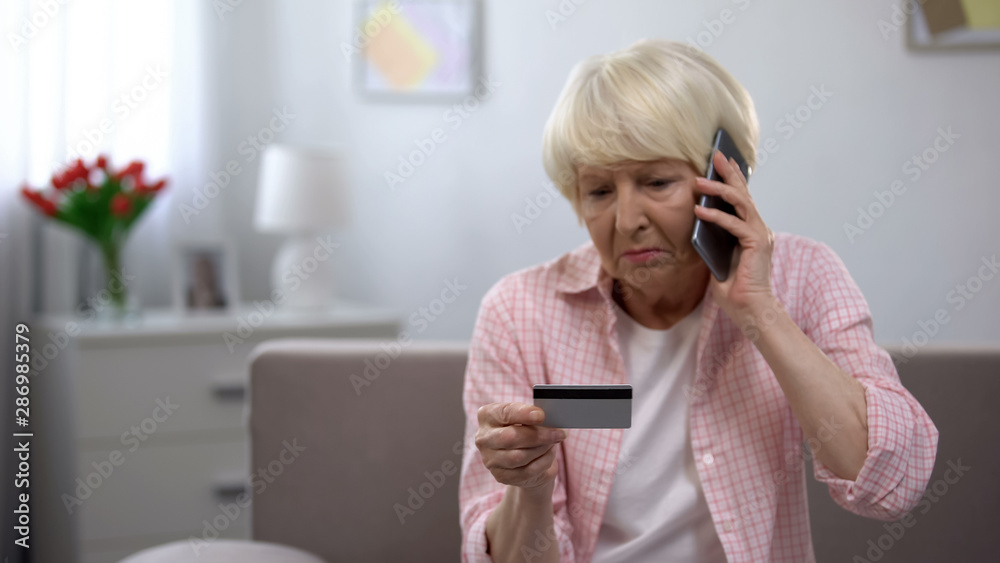 Fototapeta Sad old woman with credit card calling bank support, reporting about money fraud