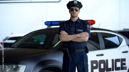 Fotomural  Brave police officer in service cap and sunglasses posing into camera near car