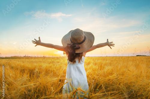 Obraz A child in a wheat field. Sunset. Selective focus. - fototapety do salonu