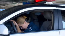 Exhausted Female Cop Officer In Police Car After Hard Work Day, Stressful Job