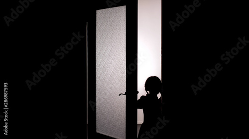 Little female child silhouette opening door into darkness, horror scene, mystic Canvas Print