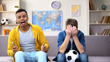 Multiracial Teenager Friends Disappointed About Favorite Football Team Losing