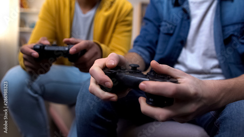Two multiethnic teenage boys playing computer games at home, hands close-up Tableau sur Toile