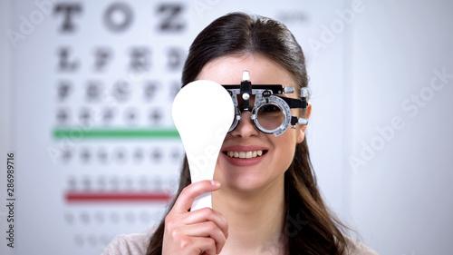 Slika na platnu Woman in phoropter closing one eye and smiling, choosing correct lens diopter