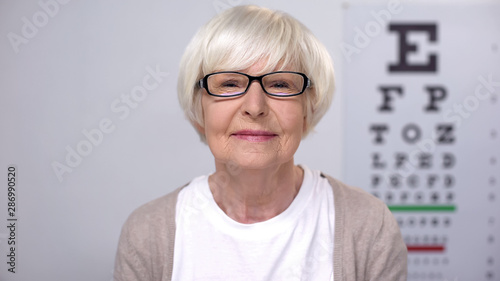 Fotomural  Senior female in eyeglasses smiling to camera, satisfied with service quality